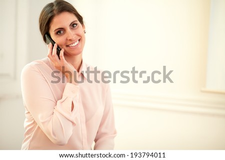 Portrait of young 30s lady on pink blouse talking on her cellphone while smiling at you on closeup background - copyspace - stock photo