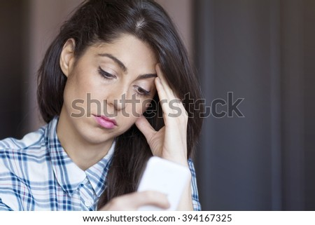 Portrait of young sad annoyed woman, receiving bad sms - stock photo