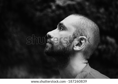 Portrait of  young sad man with short hair in forest - stock photo