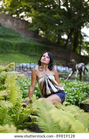 Portrait of young sadness woman which is sitting near to bush of fern in central park against sculpture of horse at Bastion hill in Riga, Latvia - stock photo