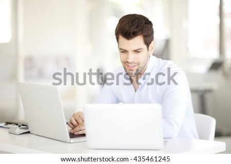 Portrait of young sales man working on laptops while sitting at office.