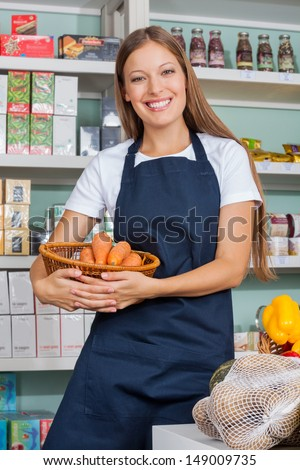 Portrait of young saleswoman holding vegetable basket in supermarket - stock photo