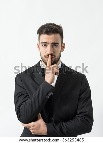 Portrait of young scared man with finger over his lips looking at camera. Desaturated portrait over gray studio background with retro vignette.  - stock photo