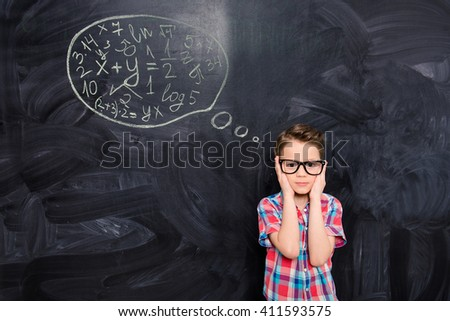 Portrait of young schoolboy in glasses trying to solve difficult task - stock photo