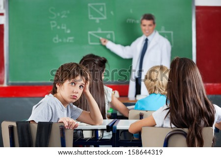 Portrait of young schoolboy leaning at desk with teacher teaching in background - stock photo