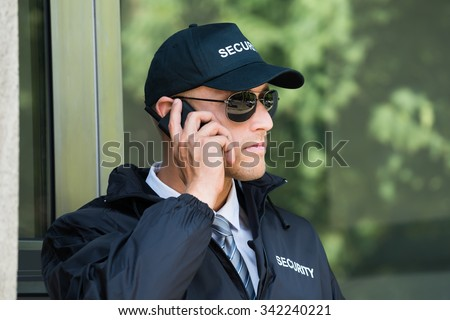 Portrait Of Young Security Guard Talking On Walkie-talkie - stock photo