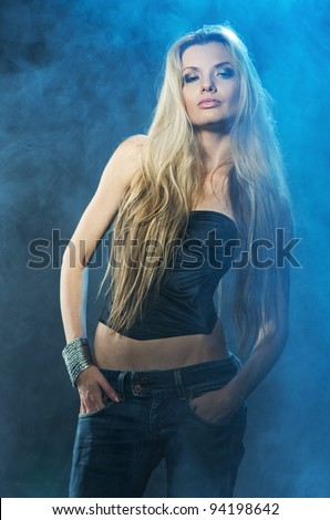Portrait of young seductive woman in the blue smoke - stock photo