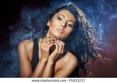 Portrait of young seductive woman in the blue smoke on the black background - stock photo