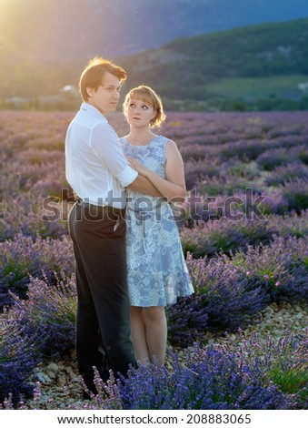 Portrait of young sensual loving couple in a lavender field at sunset backlight. Provence, France - stock photo