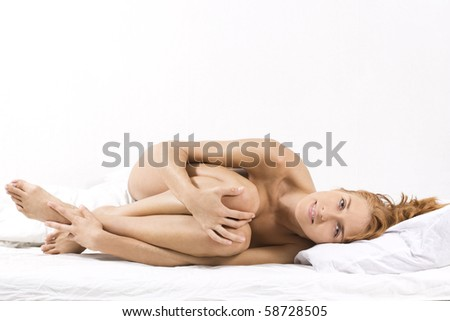 Portrait of young sensual woman lying in bed - stock photo