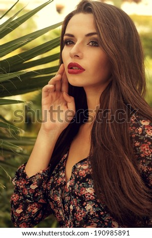 portrait of young sensual woman posing in summer dress against palm trees.  - stock photo