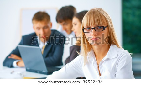 Portrait of young serious business woman with her working colleagues at the background - stock photo
