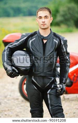 Portrait of young serious dark-haired man wearing black leather costume and holding helmet against red motorbike. - stock photo