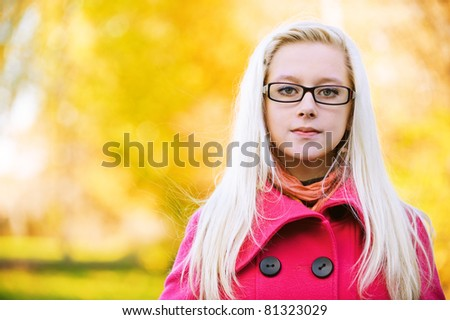 Portrait of young serious long-haired blond woman wearing eyeglasses and pink coat and standing at autumn park. - stock photo