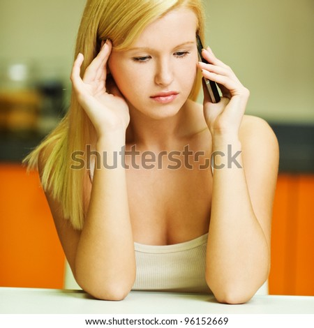 portrait of young serious woman sitting at a desk talking on the phone looking down - stock photo