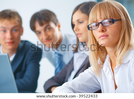 Portrait of young serious woman with her team - stock photo