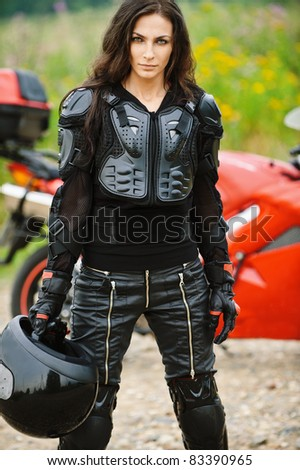 Portrait of young severe brunette woman wearing protective costume and holding helmet. standing against red motorbike. - stock photo