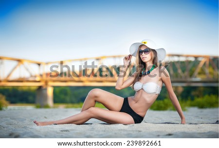 Portrait of young sexy brunette girl in swimsuit lying on the beach with a bridge in background. Sensual attractive young woman with sunglasses, hat and perfect body relaxing on the beach. - stock photo
