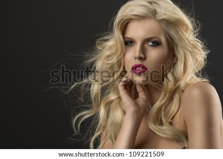 portrait of young sexy girl with blode wavy hairstyle and and flying hair from wind, she is turned of three quarters, looks in to the lens and her right hand is near the face - stock photo