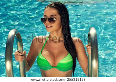 POrtrait of young sexy tanned girl posing in swimming pool in green bikini on a summer day - stock photo