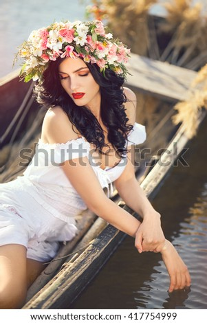 Portrait of young sexy woman on boat at sunset. The girl has a flower wreath on her head, relaxing and sailing on river. Fantasy art photography. Concept of female beauty, rest in the nature, and