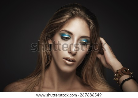 Portrait of young sexy woman while touching her hair against dark background - stock photo
