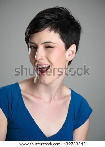 Portrait of young short hair cute woman winking at camera with open mouth