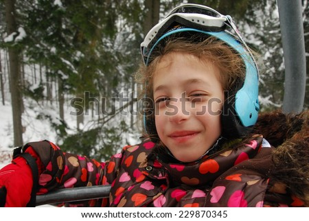 Portrait of young skier girl on a ski-lift. Skiing, winter sports. - stock photo
