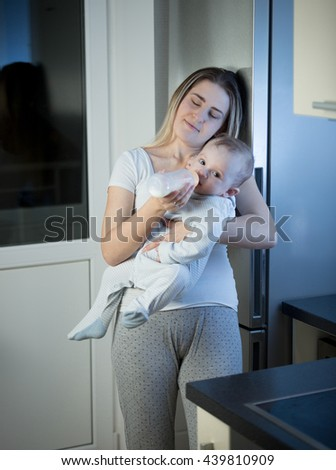 Portrait of young sleepy mother feeding baby son from bottle on kitchen at night - stock photo