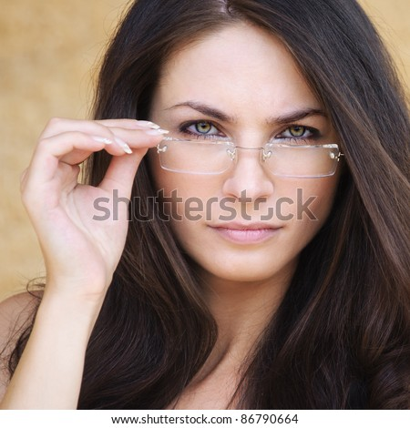 Portrait of young smart brunette woman wearing eyeglasses against yellow background.