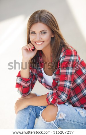 Portrait Of Young Smiling Beautiful Woman. fashionable casual woman sitting on the floor in city street. woman portrait outdoor. smiling girl portrait