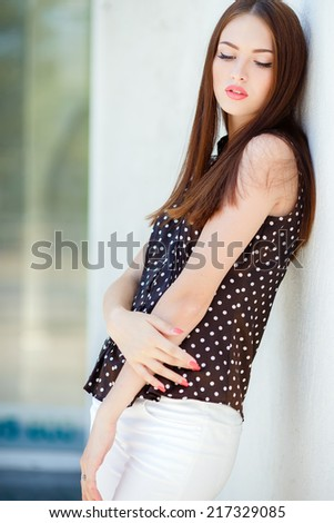 Portrait Of Young Smiling Beautiful Woman outdoor. Beautiful woman with long black hair, outdoors shot against a wall. Fashionable woman posing near white wall. Portrait of pretty young business woman - stock photo