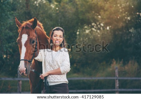 Portrait of young smiling beautiful woman walking with brown horse outdoors - stock photo