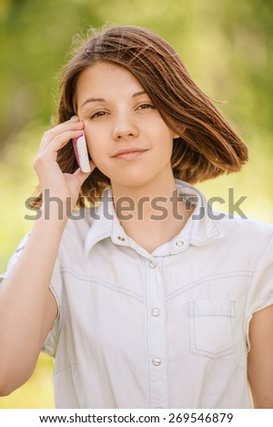Portrait of young smiling brunette woman wearing white shirt and speaking on telephone at summer green park. - stock photo