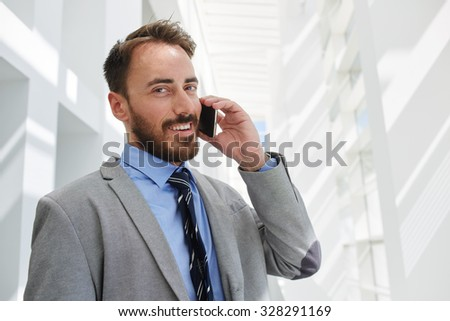 Portrait of young smiling business man bookkeeper talking on smart phone while standing in hallway of his company, cheerful intelligent male economist dressed in luxury suit speaking on cell telephone - stock photo