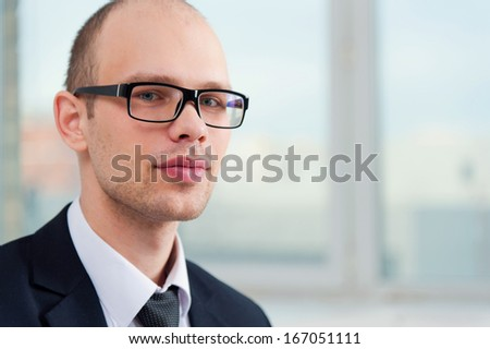 Portrait of young smiling business man wearing glasses in office with view to window - stock photo
