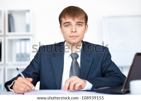 Portrait of young smiling business man writing on paperwork in office - stock photo