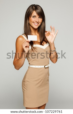 Portrait of young smiling business woman holding credit card and showing OK sign - stock photo