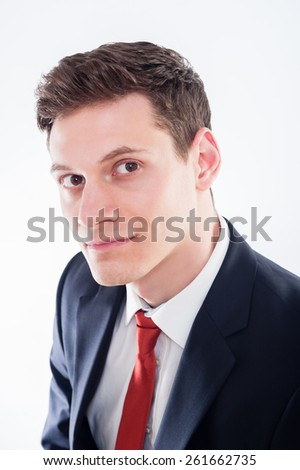 Portrait of young  smiling businessman in black suit and red tie on white background - stock photo
