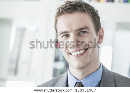 Portrait of young smiling businessman looking at camera - stock photo