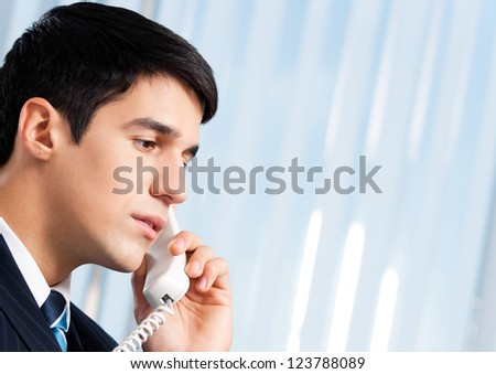 Portrait of young smiling businessman or call center worker with phone at office