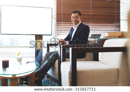 Portrait of young smiling businessman use digital tablet while preparing for meeting with colleagues, cheerful intelligent man sitting with touch pad near empty screen with copy space for your content - stock photo