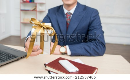 Portrait of young smiling businessman  with a present box in office sitting on the desk working on computer, looking at camera, selective focus on a gift box - stock photo