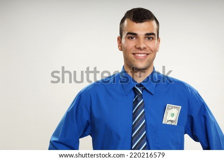 Portrait of young smiling businessman with one dollar banknote in pocket - stock photo