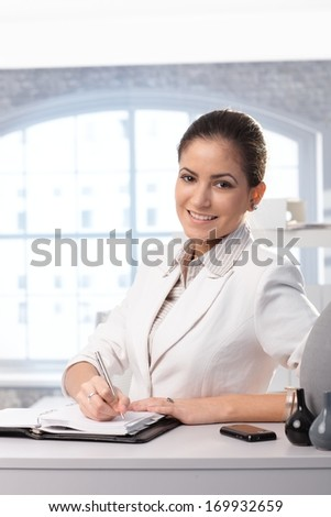 Portrait of young smiling businesswoman writing into personal organizer in office. - stock photo