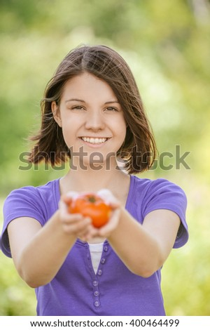 Portrait of young smiling cheerful brunette woman in violet blouse holding tomato at summer green park. - stock photo
