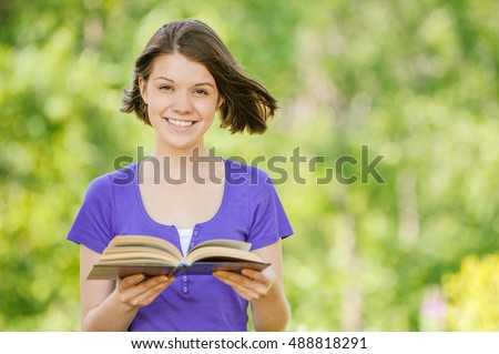 Portrait of young smiling cheerful woman in violet blouse reading interesting book at summer green park.