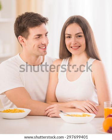 Portrait of young smiling couple having breakfast in the kitchen.
