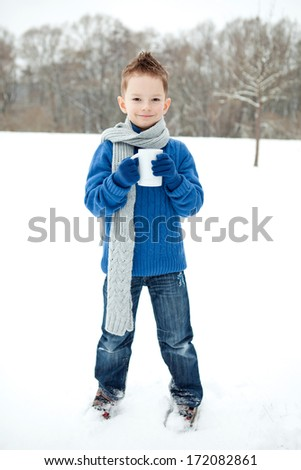 Portrait of young smiling cute frozen boy in a scarf and with cup - stock photo