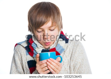 Portrait of young smiling cute frozen teenager in a scarf and with blue cup, isolated on white - stock photo